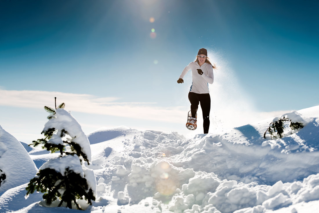 Athletic woman running through deep snow with snowshoes on a sunny day.